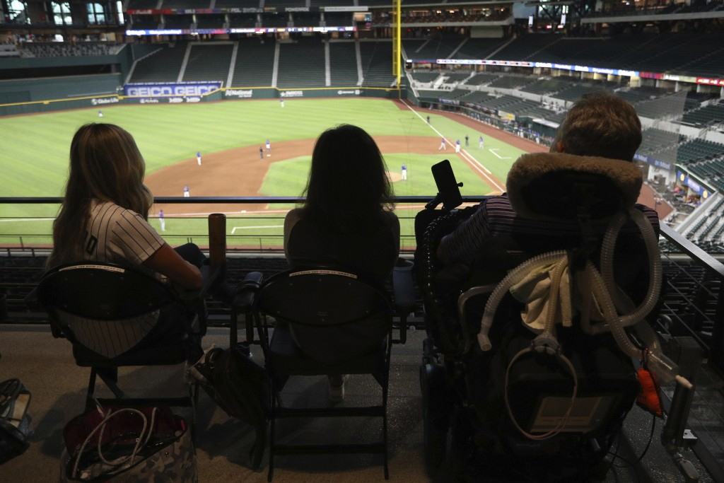 Kat Minnerly, Tamara Hilliard, and Jim Hilliard watch the Colorado Rockies play against the Texas Rangers in an exhibition baseball game Tuesday, July...