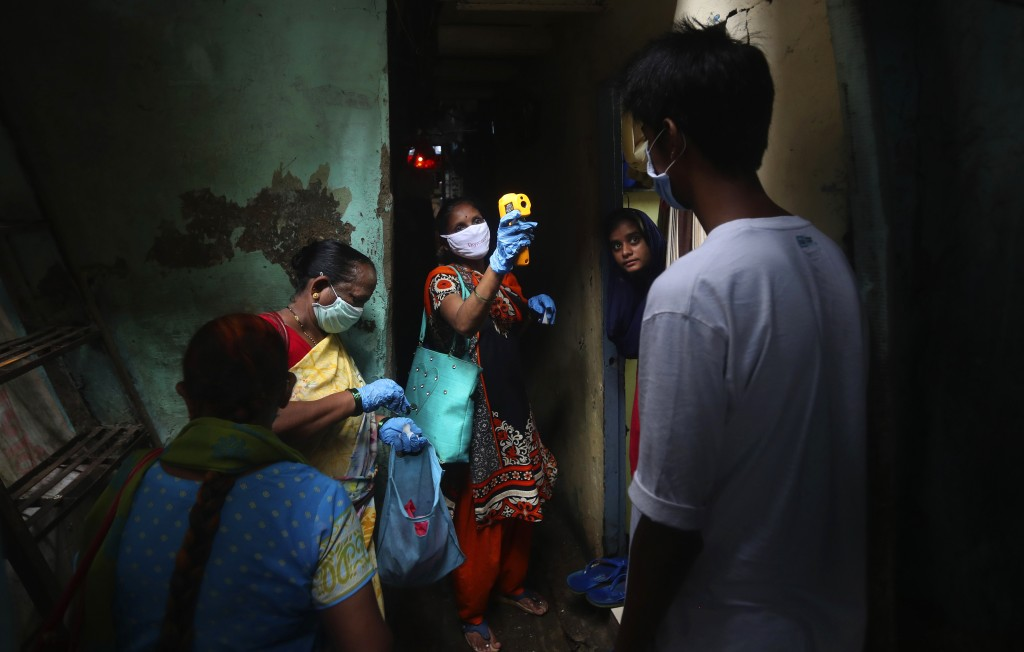 FILE - In this July 6, 2020, file photo, a health worker screens people for COVID-19 symptoms at Dharavi, one of Asia's biggest slums, in Mumbai, Indi...
