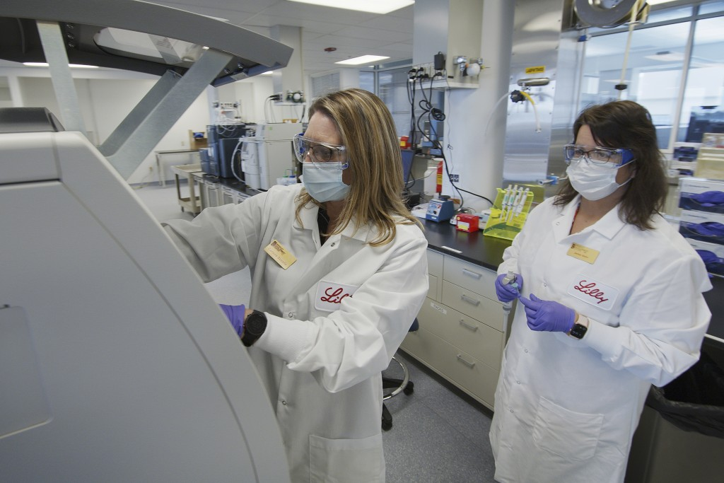 In this May 2020 photo provided by Eli Lilly, researchers prepare cells to produce possible COVID-19 antibodies for testing in a laboratory in Indiana...