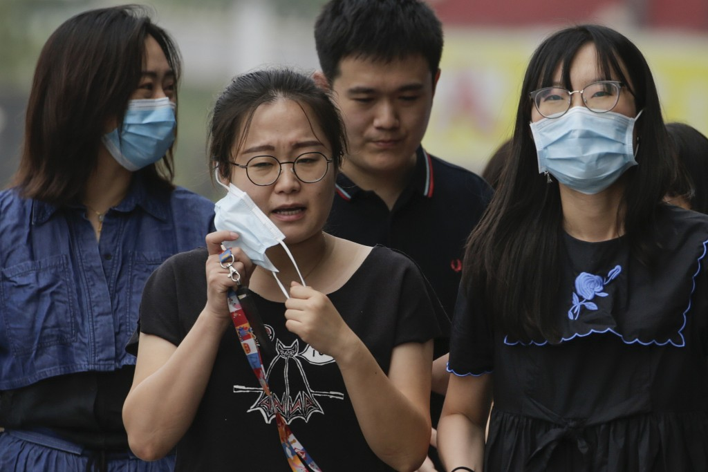 A woman takes off her face mask next to her colleagues wearing face masks to protect against the new coronavirus as they walk on a street in Beijing, ...
