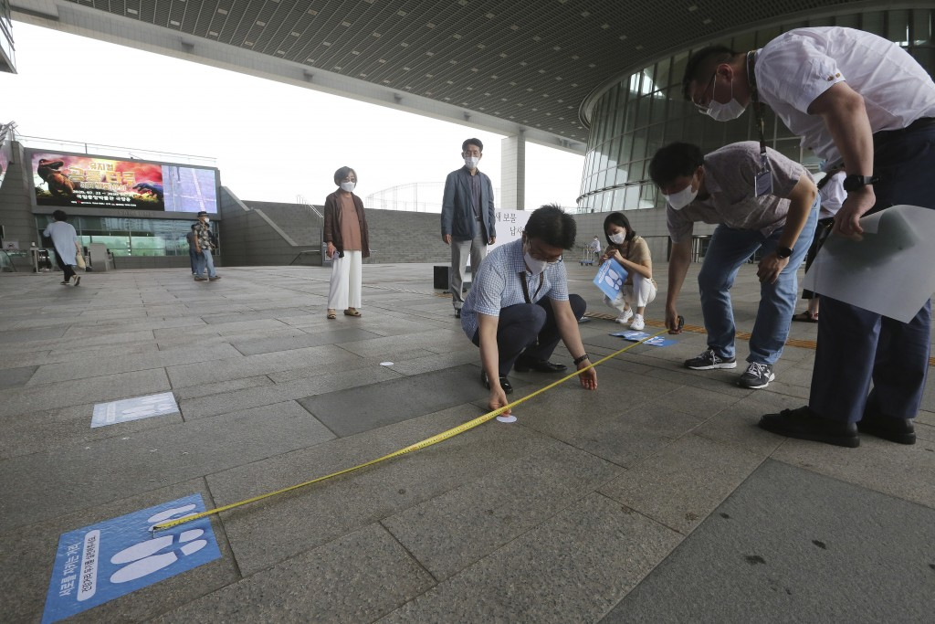 Employees measure the distance to attach social distancing signs on the floor at the National Museum of Korea in Seoul, South Korea, Wednesday, July 2...