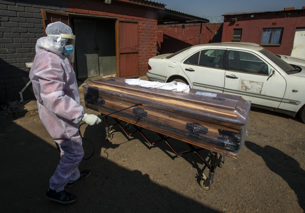 A funeral home worker in A protective suit disinfects a coffin carrying a woman who died from COVID-19, as they prepare for a funeral in Katlehong, ne...
