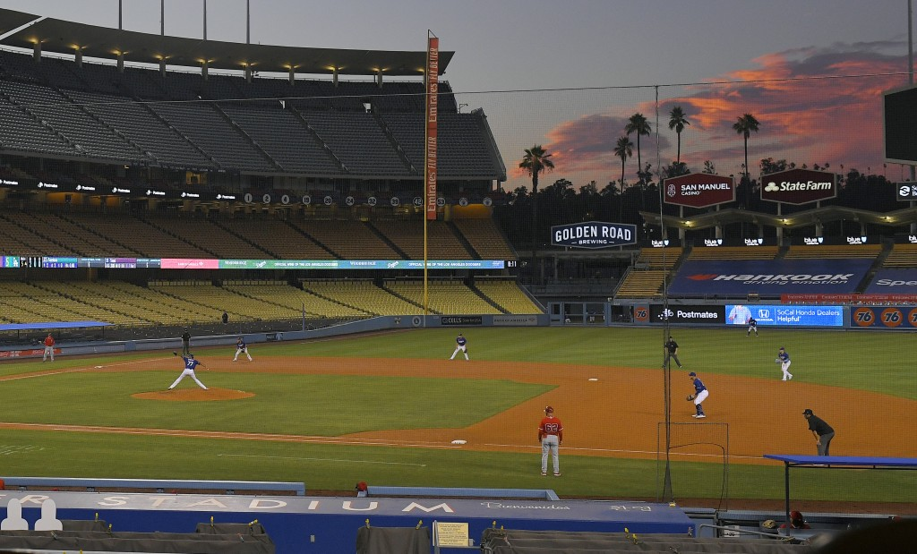 The Los Angeles Dodgers play the Los Angeles Angels at sunset during the fifth inning of a preseason baseball game, Tuesday, July 21, 2020, in Los Ang...