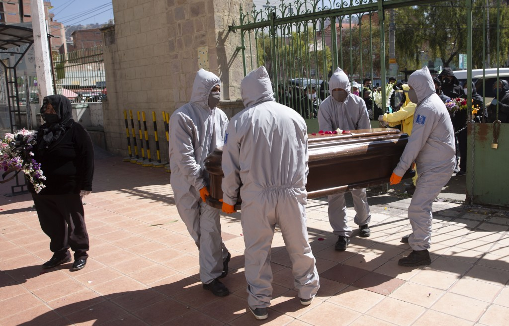 Funeral home workers wearing full protective gear as a precaution against the spread of the new coronavirus, carry the coffin of a man, whose death wa...