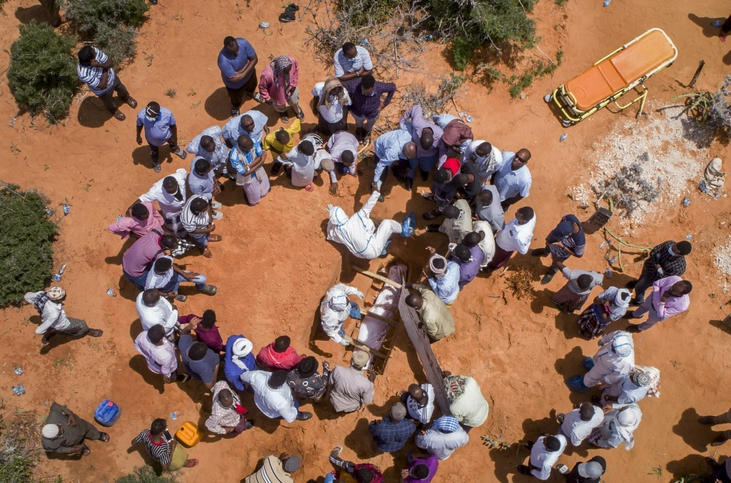 FILE - In this April 30, 2020, file photo, medical workers in protective suits bury the body of an elderly man believed to have died from the coronavi...