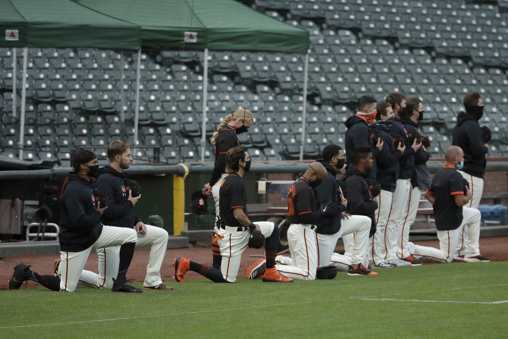 San Francisco Giants players and coaches kneel with others during the national anthem before an exhibition baseball game against the Oakland Athletics...