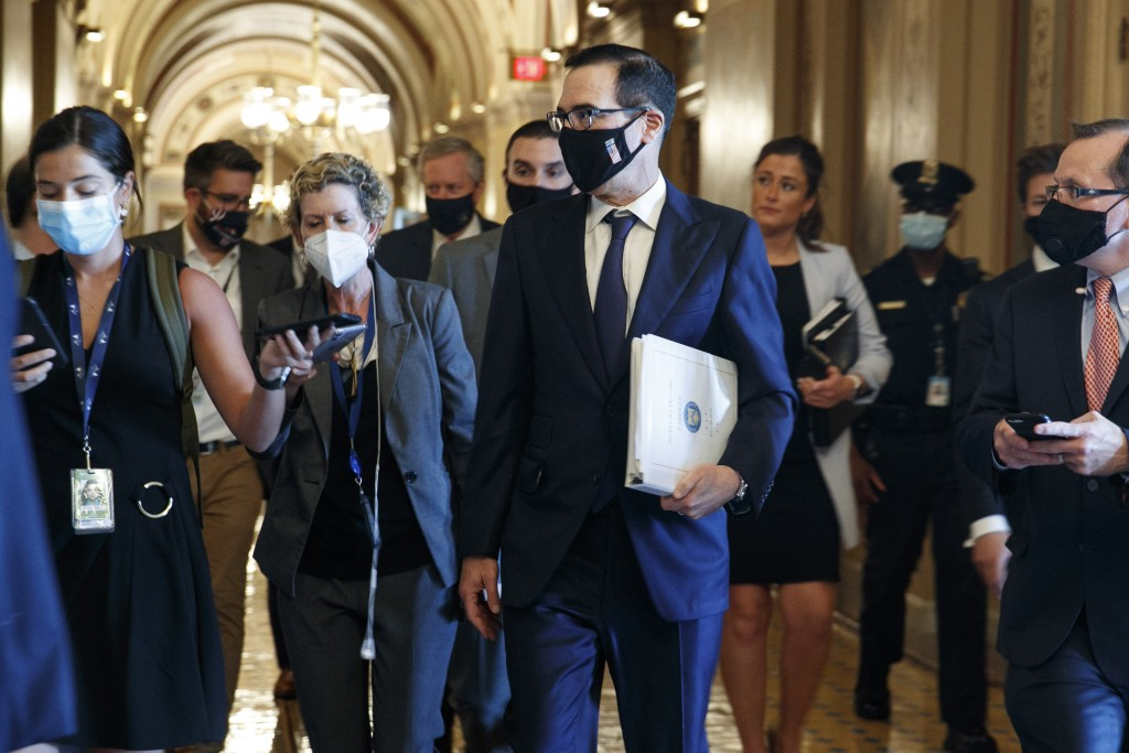 Treasury Secretary Steven Mnuchin , center, walks to a Republican luncheon, Tuesday, July 21, 2020, while attending meetings on Capitol Hill in Washin...