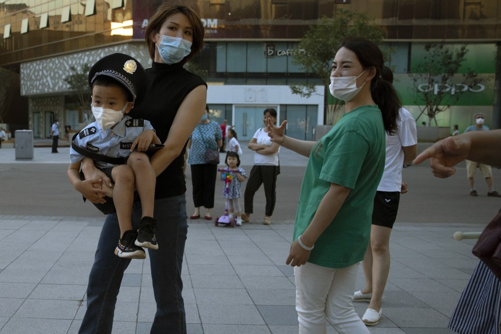 A woman holds a child dressed like a policeman as they wear masks to curb the spread of the coronavirus in Beijing, China on Tuesday, July 21, 2020. E...