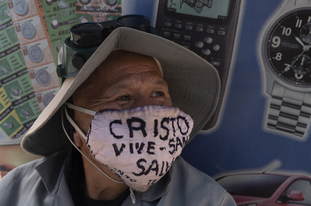 """A man wearing a protective face mask marked with a message that reads in Spanish: """"Christ lives, heals and saves,"""" in La Paz, Bolivia, Tuesday, July 2..."""