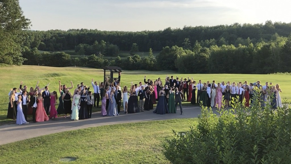 In this Saturday, July 18, 2020, image provided by Carol Justic, recent Bedford High School graduates and students pose for a photo at their outdoor p...