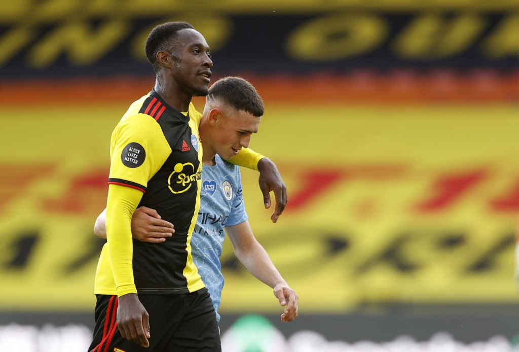 Watford's Danny Welbeck, front, and Manchester City's Phil Foden leave the field at the end of the English Premier League soccer match between Watford...