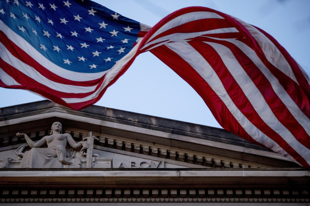 FILE - In this March 22, 2019 file photo, an American flag flies outside the Department of Justice in Washington. The Justice Department has accused t...