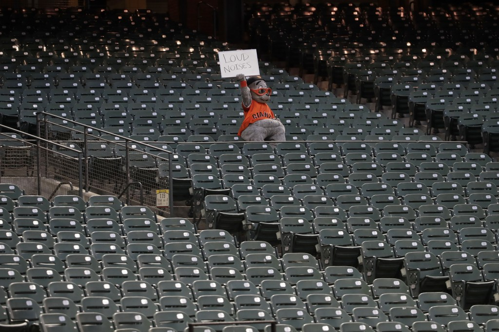 San Francisco Giants mascot Lou Seal holds up a sign during the fifth inning of an exhibition baseball game between the Giants and the Oakland Athleti...