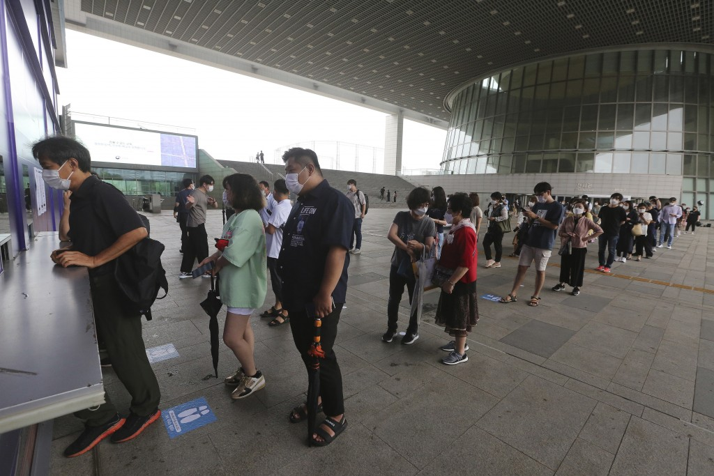 Visitors wearing face masks wait in line to buy tickets to enter an exhibition hall at the National Museum of Korea in Seoul, South Korea, Wednesday, ...