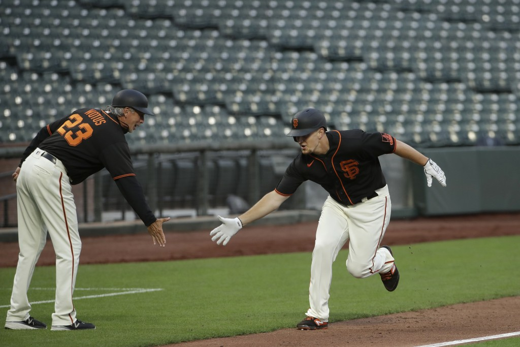 San Francisco Giants' Alex Dickerson, right, celebrates with third base coach Ron Wotus after hitting a home run off of Oakland Athletics pitcher Mike...