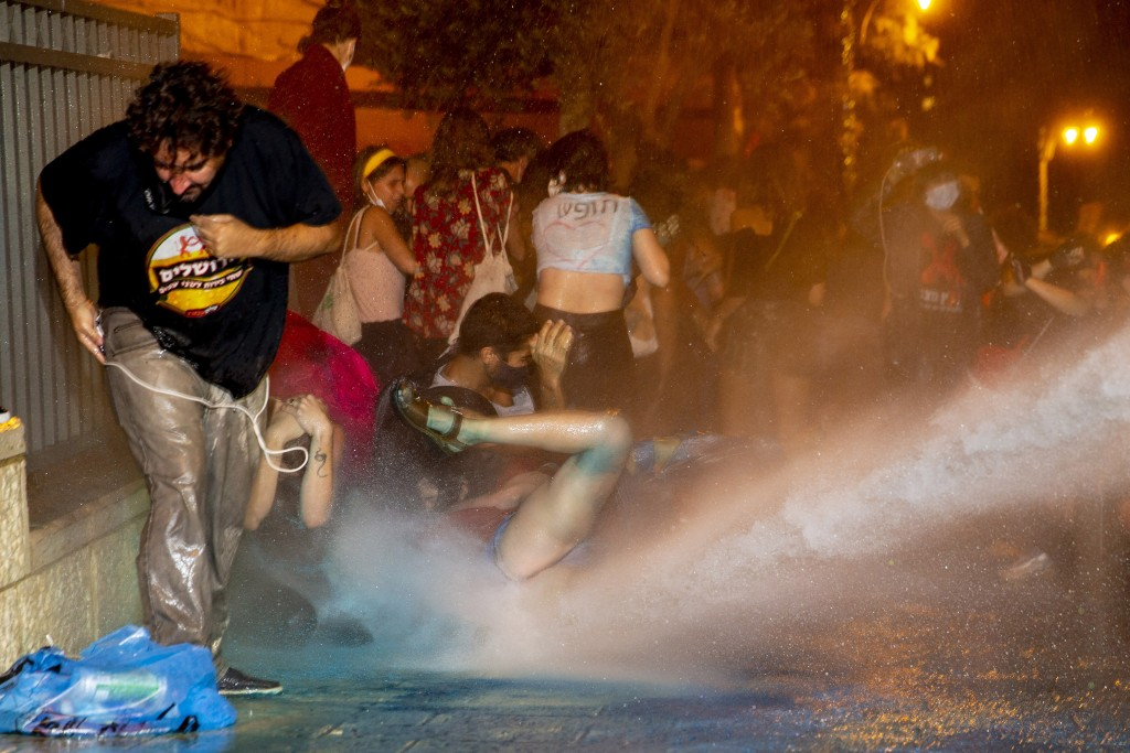 Police use a water cannon to disperse demonstrators during a protest against Israel's Prime Minister Benjamin Netanyahu outside his residence in Jerus...