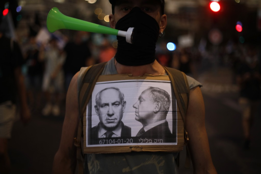 A protester wears a face mask to protect against the coronavirus during a protest against Israel's Prime Minister Benjamin Netanyahu in front of the K...