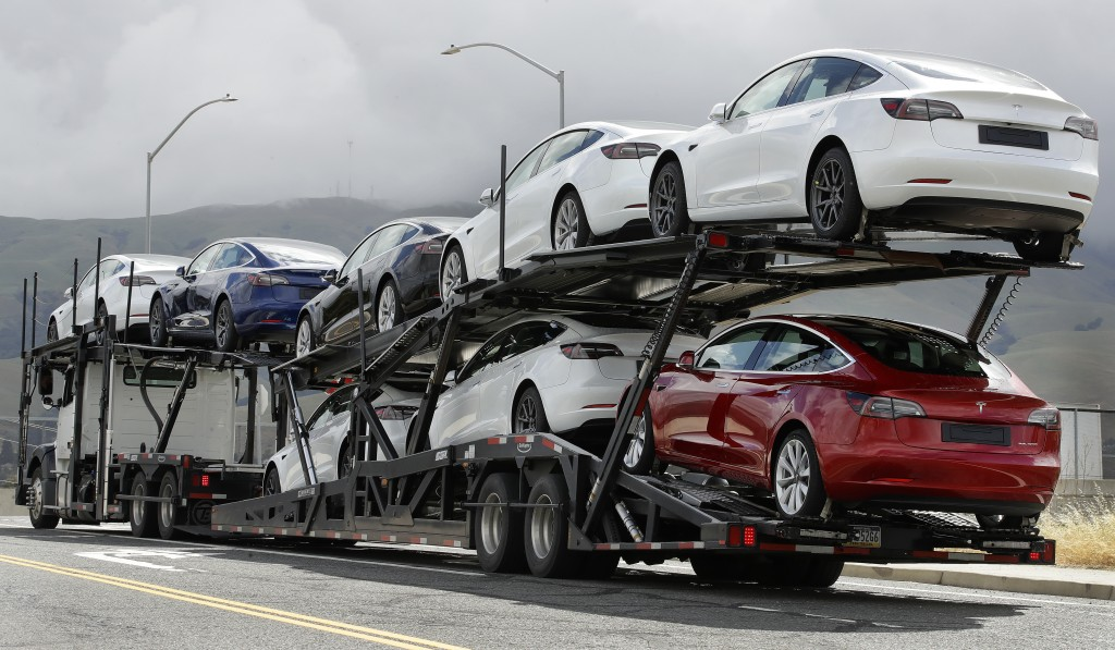 FILE - In this May 12, 2020 file photo, a truck loaded with Tesla cars departs the Tesla plant in Fremont, Calif.  Tesla has posted three straight pro...