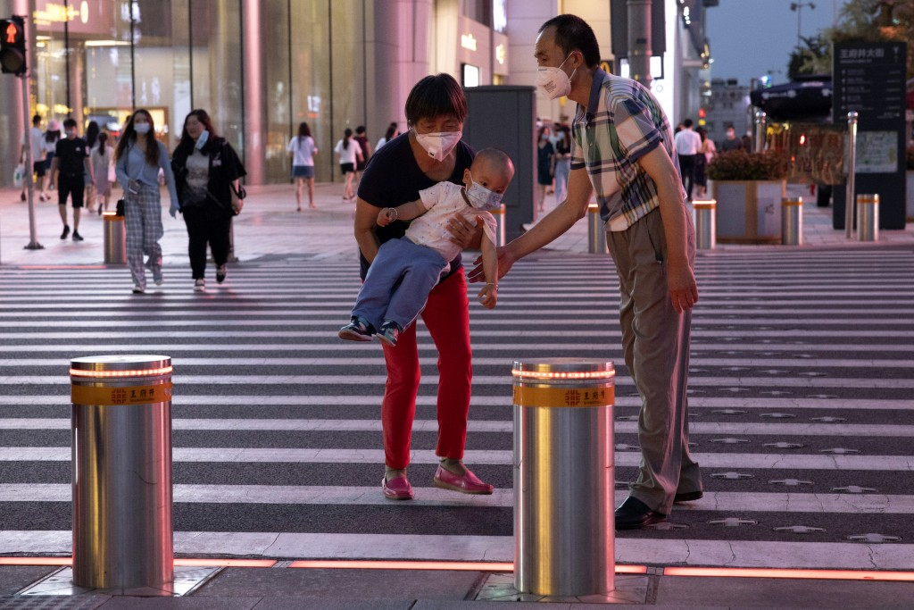 A woman carries a child across a traffic junction as they both wear masks to curb the spread of the coronavirus in Beijing, China on Tuesday, July 21,...