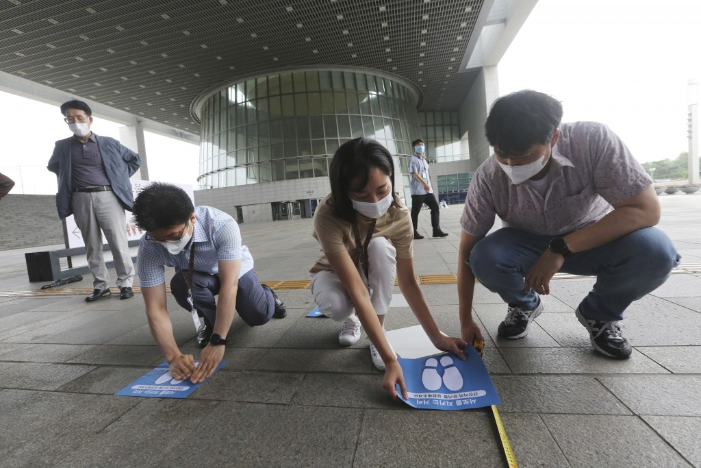 Employees attach social distancing signs on the floor at the National Museum of Korea in Seoul, South Korea, Wednesday, July 22, 2020. The museum reop...