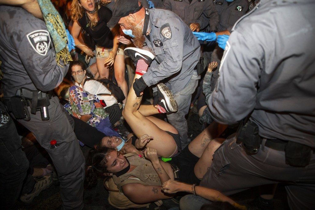 Israeli police scuffle with demonstrators during a protest against Israel's Prime Minister Benjamin Netanyahu outside his residence in Jerusalem, earl...
