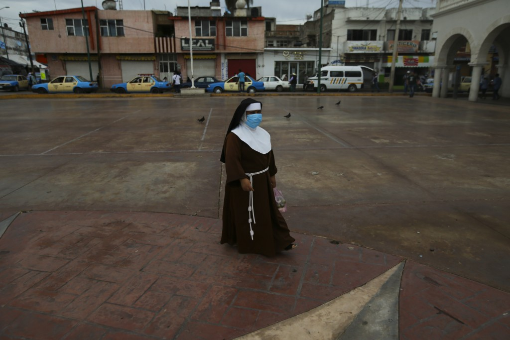 A nun wearing a mask amid the COVID-19 pandemic walks at the main square in Acatlán de Osorio, a town in Mexico where the life blood is remittances fr...