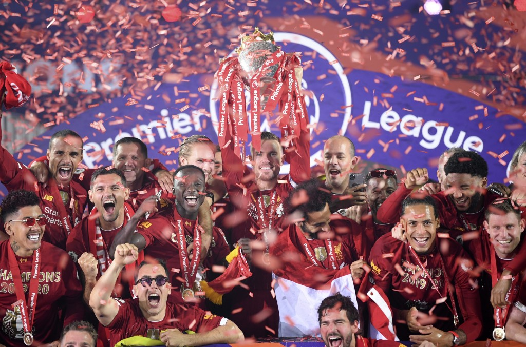 Liverpool's Jordan Henderson lifts the English Premier League trophy following the English Premier League soccer match between Liverpool and Chelsea a...
