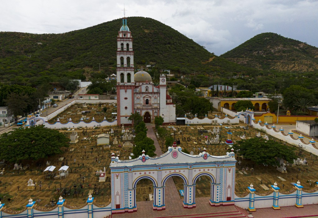 Graves surround the church of San Jeronimo Xayacatlan, Mexico, a town from which nearly a third of residents have emigrated to New York, Friday, June ...