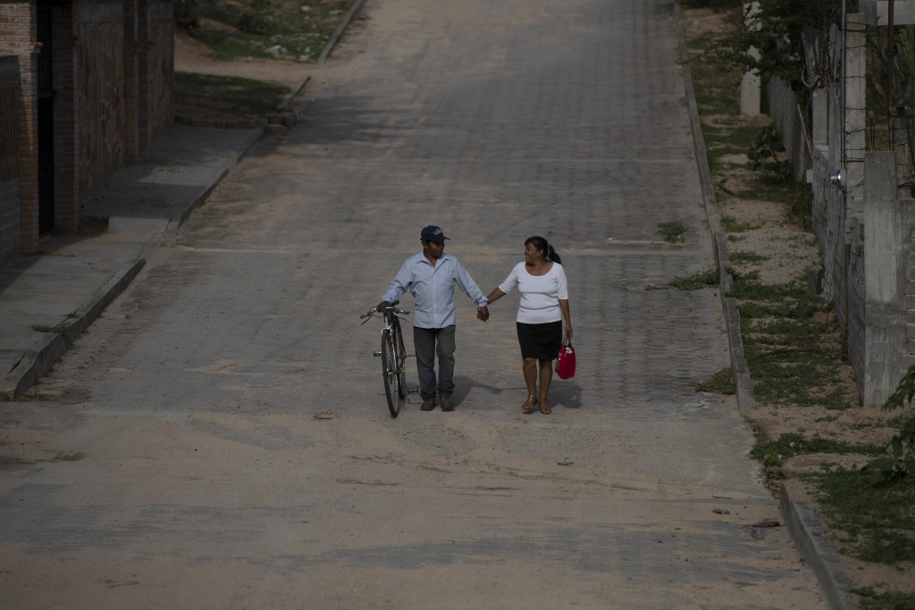 A couple walks hand in hand through San Jeronimo Xayacatlan, a town in Mexico from where nearly a third have emigrated to New York, Friday, June 26, 2...
