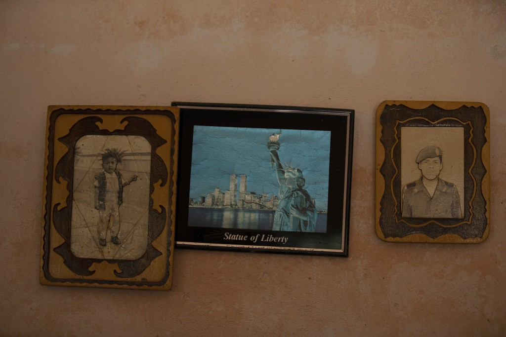 Photographs of Jorge Vazquez, left, and his brother Orlando Vazquez flank an image of the Statue of Liberty in New York, inside the home of their moth...