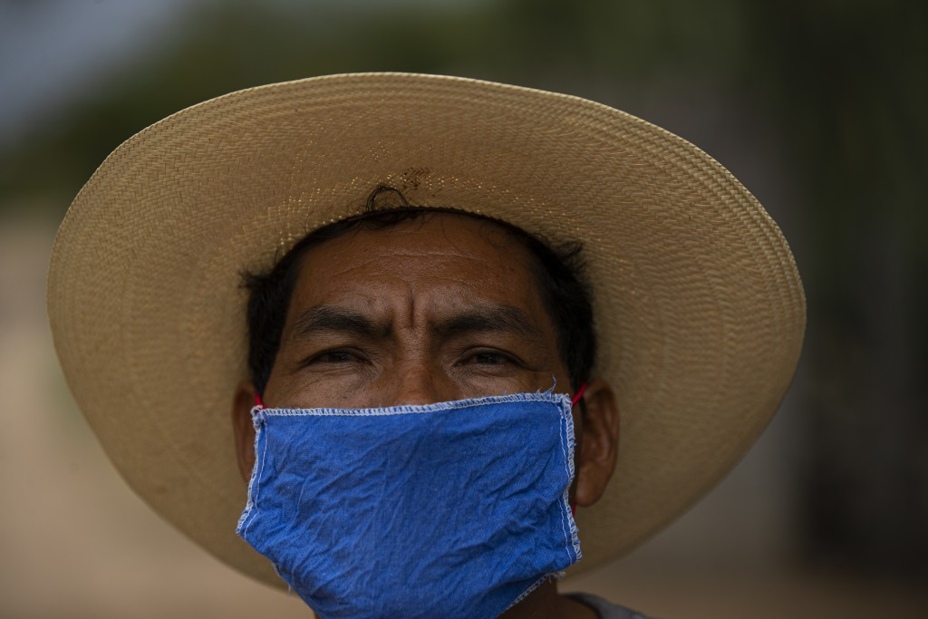 Jorge Vazquez wears a face mask amid the spread of COVID-19 outside his home in San Jeronimo Xayacatlan, a town in Mexico from where nearly a third ha...