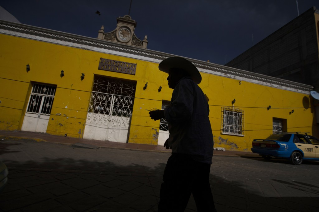 A customer leaves a bank where people receive international money wires in Acatlan de Osorio, Mexico, Saturday, June 27, 2020. In April and May, as th...