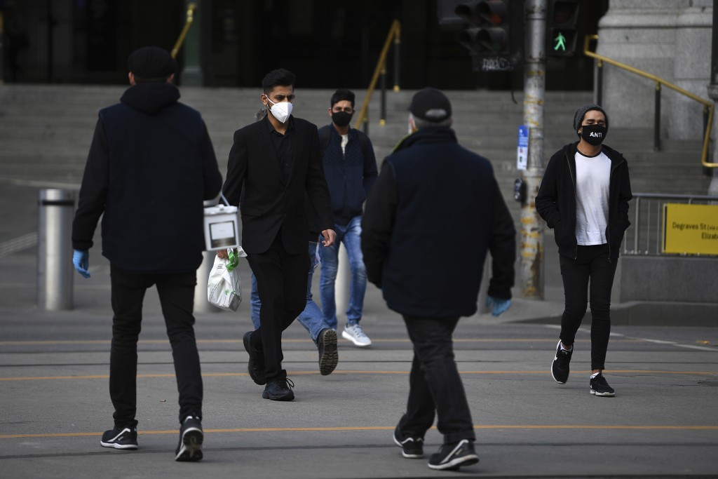 People wearing face masks to help protect against the spread of the new coronavirus walk outside Flinders Street Station in Melbourne, Australia, Thur...