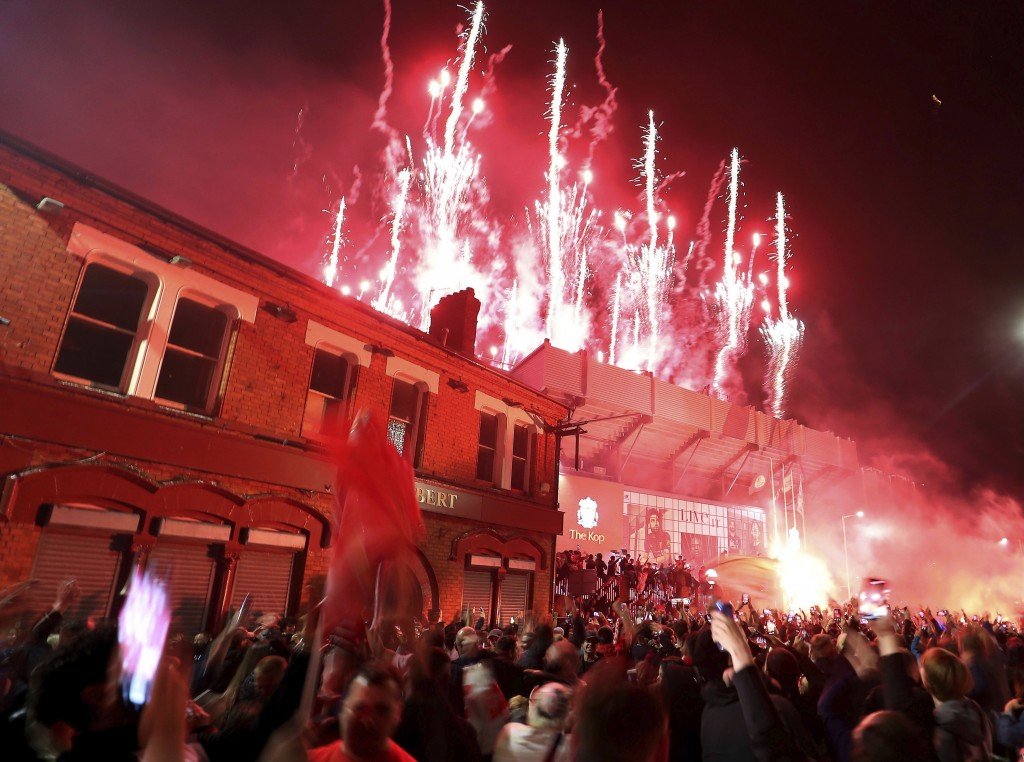 Liverpool fans celebrate outside Anfield stadium as fireworks are set off as the players receive the Premier League trophy inside the grounds after th...