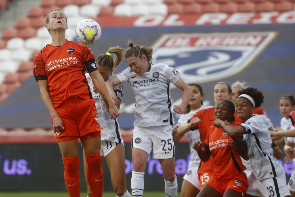 Houston Dash's Sophie Schmidt, left, battles for a head ball with Portland Thorns' Rocky Rodriguez (11) and Meghan Klingenberg (25) during the first h...