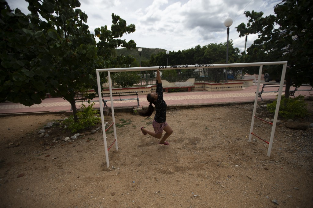 A girl plays at the park in San Jeronimo Xayacatlan, a town in Mexico from where nearly a third have emigrated to New York, Thursday, June 25, 2020. M...