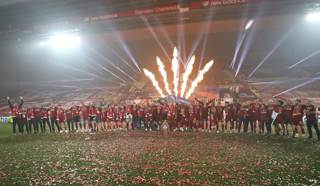 Fireworks explode behind as Liverpool's Jordan Henderson and team members celebrate with the English Premier League trophy aloft after it was presente...