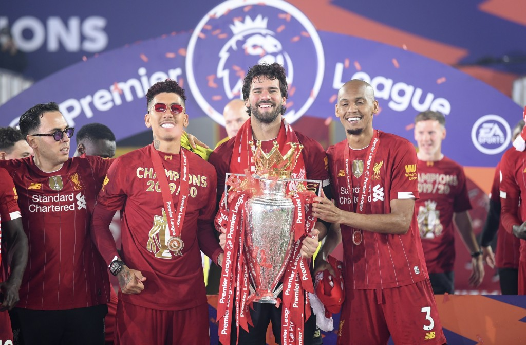 Liverpool's Fabinho, right, Liverpool's goalkeeper Alisson, center, and Roberto Firmino, all from Brazil, celebrate with the English Premier League tr...