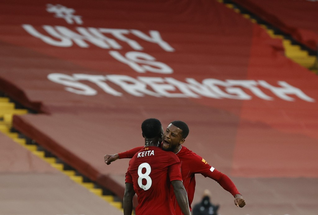 Liverpool's Naby Keita, no 8, turns away to celebrate after scoring the opening goal of the game with teammateLiverpool's Georginio Wijnaldum during t...