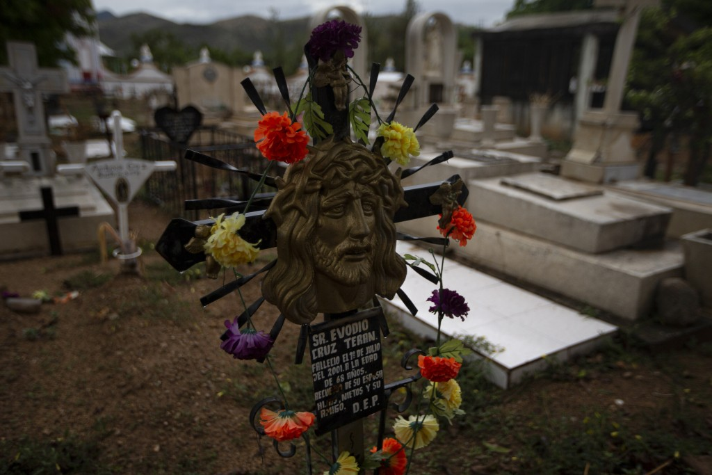 A sculpture of Jesus stands as a headstone at the cemetery in San Jeronimo Xayacatlan, a town in Mexico from where nearly a third have emigrated to Ne...