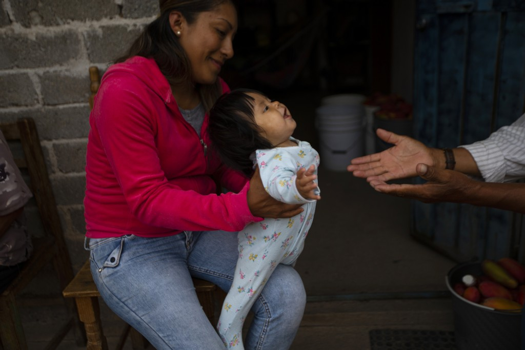 Nataly Ortega, whose mother Magnolia Ortega works cleaning homes in Staten Island, New York, holds her niece Azul in San Jeronimo Xayacatlan, Mexico, ...