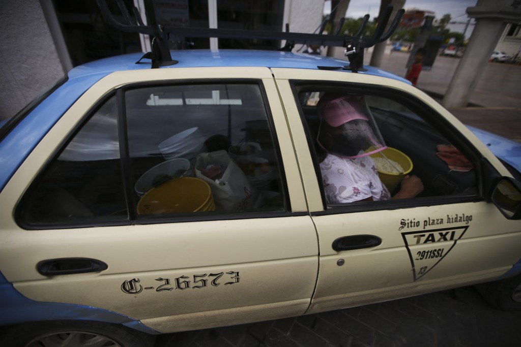 A food vendor wearing a face shield amid the COVID-19 pandemic uses a taxi to transport her materials in Acatlán de Osorio, a town in Mexico where the...