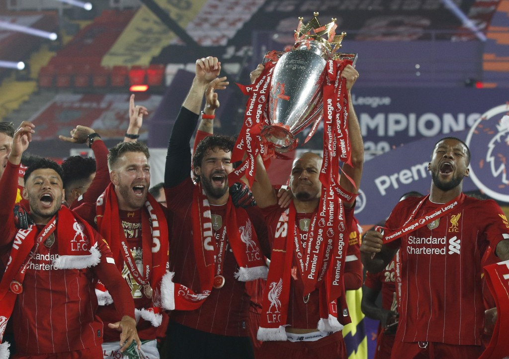 Liverpool's Fabinho and team members celebrate with the English Premier League trophy after it was presented following the Premier League soccer match...