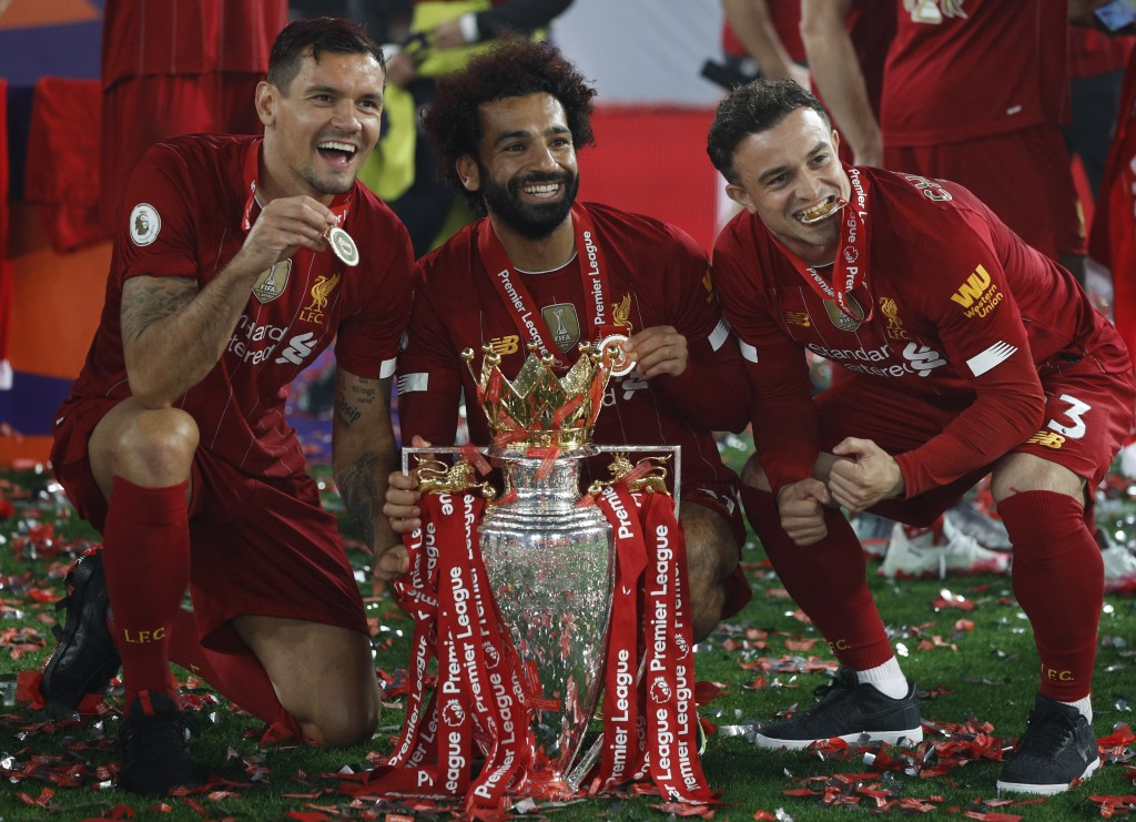 Liverpool's Mohamed Salah, ceter, and Liverpool's Xherdan Shaqiri, right, and Liverpool's Dejan Lovren pose with the English Premier League trophy fol...