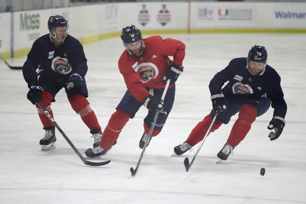 Florida Panthers center Lucas Wallmark, left, right wing Brett Connolly, center, and defenseman Mike Matheson battle for the puck during NHL hockey pr...