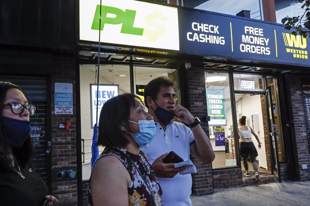 Magnolia Ortega, center, stands outside a Western Union with her husband Arturo Morales and their daughter Marlene after wiring money to her family in...