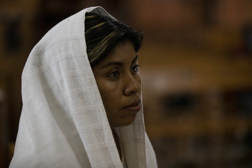 A woman attends Mass at church in San Jeronimo Xayacatlan, a town in Mexico from where nearly a third have emigrated to New York, Thursday, June 25, 2...