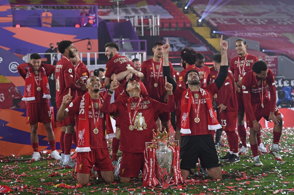 Liverpool's Fabinho, left, Liverpool's goalkeeper Alisson, right, and Roberto Firmino, all from Brazil, celebrate with the English Premier League trop...