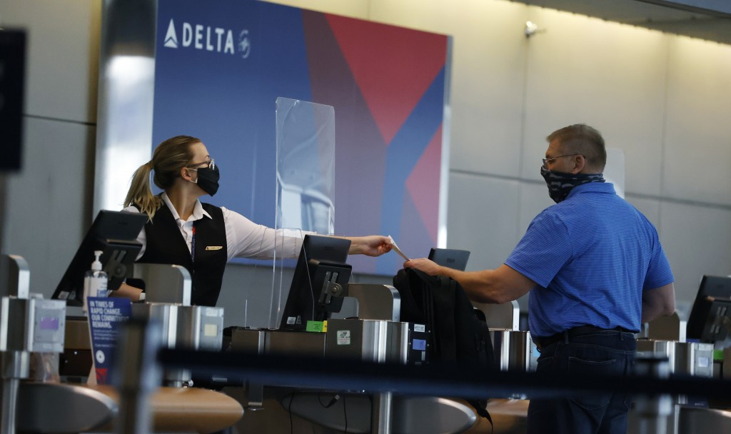 FILE - In this July 22, 2020 photo, a ticketing agent for Delta Airlines hands a boarding pass to a passenger as he checks in for a flight in the main...