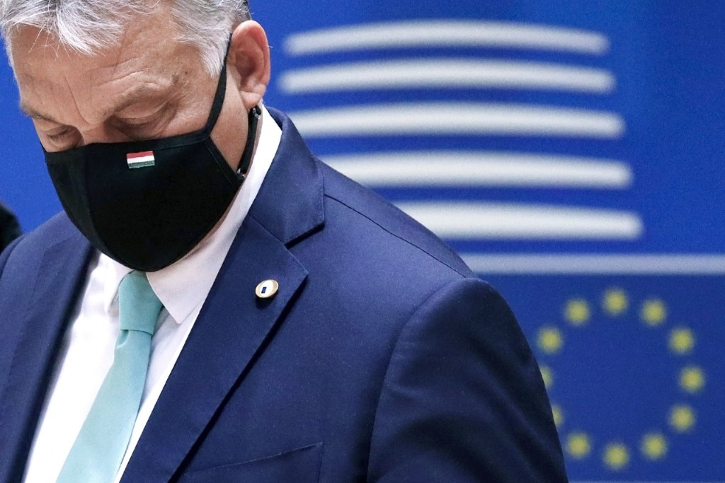 FILE- In this Saturday, July 18, 2020, file photo, Hungary's Prime Minister Viktor Orban wears a protective face mask as he arrives for a round table ...